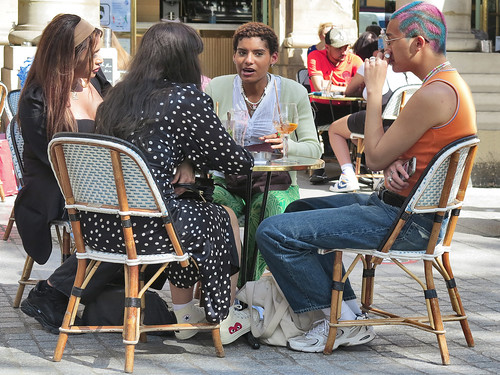 Customers seated at a table on Place Colette