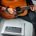 Close-up of male music coach or tutor play guitar have online video lesson on laptop at home. Top view.