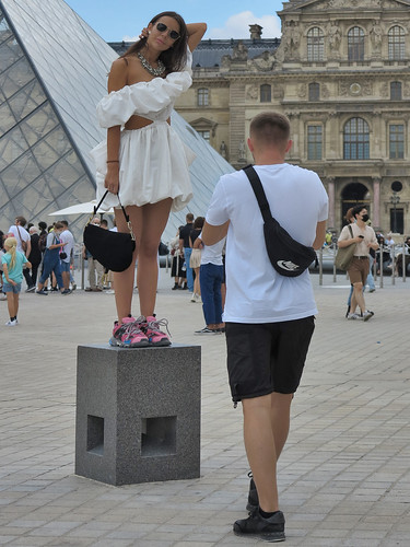 Girl in elegant white dress posing in front of the Louvre Pyramid