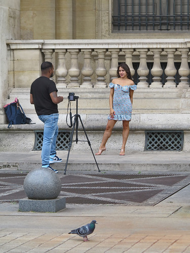 Photographer and model at work in front of the Louvre Pyramid