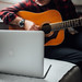 Close-up of male music coach or tutor play guitar have online video lesson on Macbook at home. Closeup view.