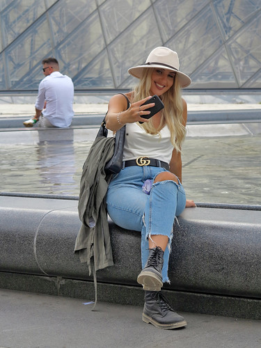 Girl in ripped jeans and hat posing for a selfie