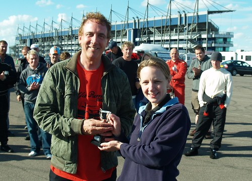 Andy Robinson receives trophy for 3rd in C at Rockingham from Emma Karwacki