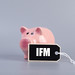Piggybank and label with IFM text on grey background